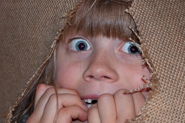 Девочка исспугано смотрит в дыру из ткани фото